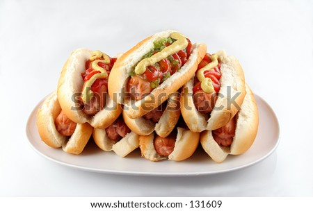 Plate of stacked hotdogs.  Ketchup, mustard, and relish. - stock photo