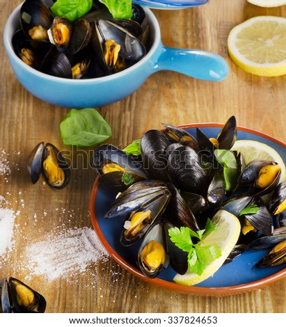 Plate of steamed mussels on a wooden background. Selective focus - stock photo