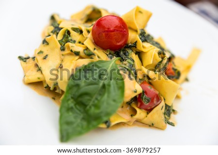 plate of tagliatelle with tomatoes and fresh basil and pesto - stock photo