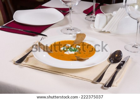 Plate of tasty pumpkin or butternut soup with cheese, melba toast and herbs served at table on a formal place setting with silverware and wineglasses - stock photo
