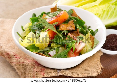 Plate of traditional Arabic salad fattouch on a wooden plate - stock photo