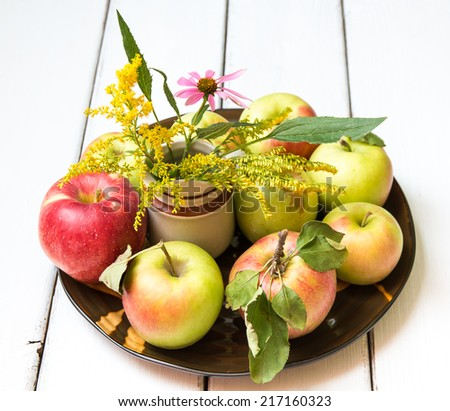 Plate of variates of fresh apples including jonagold and mutsu  and a vase with wildflowers on wooden table, autumn still life. - stock photo