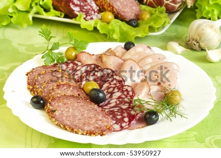 Plate of various sausages with olives - stock photo