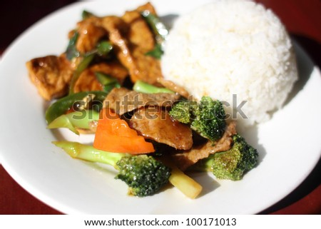 Plate of vegan Chinese food with tofu, seitan with broccoli, and rice. - stock photo