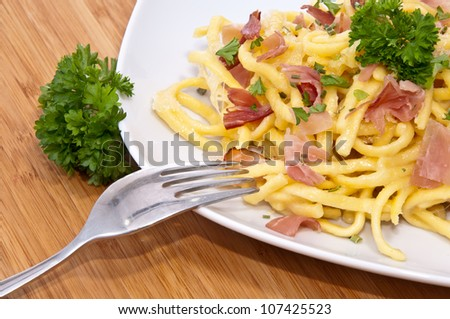 Plate with Cheese Spaetzle and cutlery on wooden background - stock photo