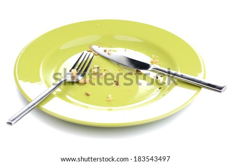 Plate with crumbs and used fork and knife, close-up, on white background - stock photo
