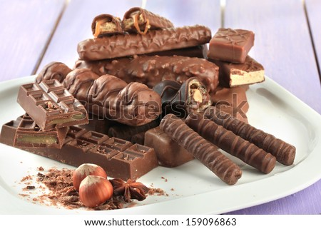 Plate with delicious chocolate bars on wooden background - stock photo