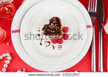 Plate with dessert in form of heart on celebratory table in honor of Valentine's Day close-up - stock photo