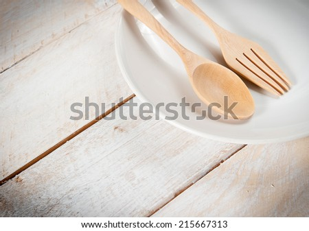 plate with fork and spoon on white wood - stock photo
