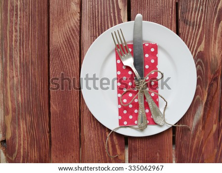 plate with fork,knife  tied with a ribbon and napkin on wooden table - stock photo