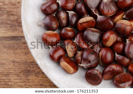 Plate with fresh Sweet Chestnuts from the Forest in Autumn - stock photo