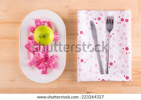 plate with green apple and measure tape in diet concept on wooden desk. Above view - stock photo