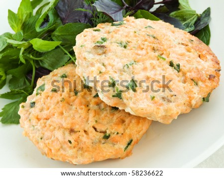 Plate with homemade salmon cutlets and herbs. Shallow dof. - stock photo