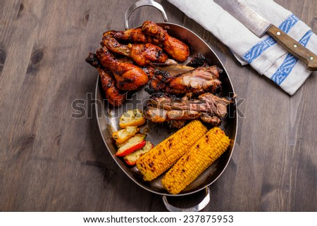 Plate with mixed bbq pork chicken corn - stock photo