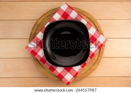 plate with napkin at cutting board on wooden background - stock photo
