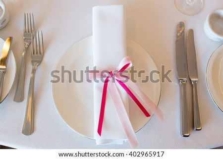 Plate with napkin with pink ribbon on wedding table in restaurant - stock photo