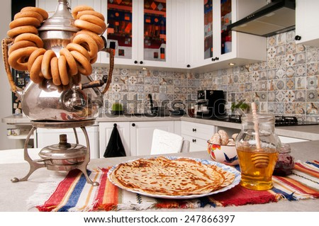 Plate with pancakes and samovar on the kitchen table - stock photo