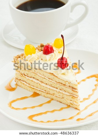 Plate with piece of cream cake and coffee cup. Shallow dof. - stock photo
