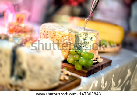 Plate with pieces of various types of cheese, white grapes and red whine at cocktail party - stock photo