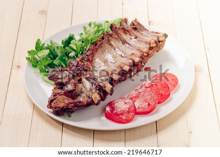 Plate with roasted pork ribs - stock photo