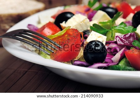 Plate with salad on table - stock photo