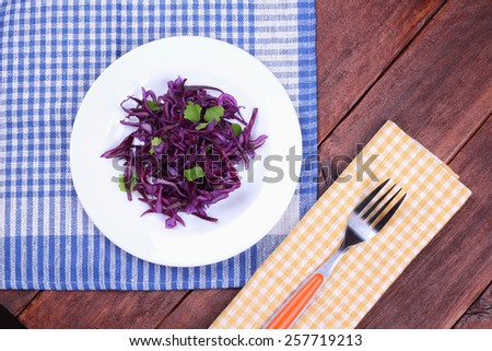 Plate with salad on the table. Plate, fork, napkin on the table. Dietary salad of red cabbage on the table. Vegetarian food. - stock photo