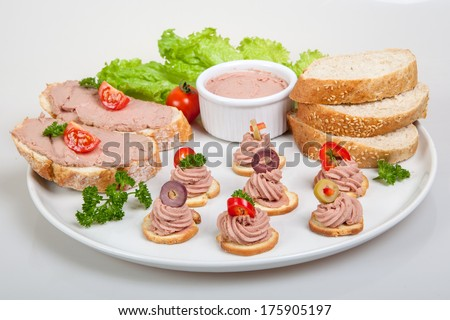 plate with slices of bread with home made pate, decorated with vegetables - stock photo