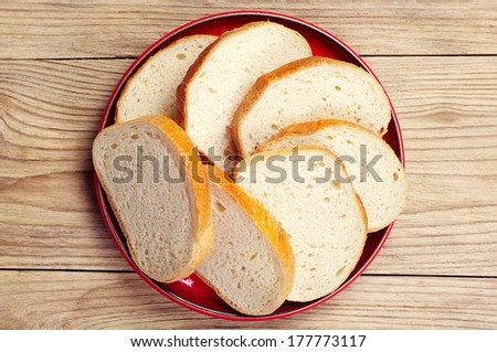 Plate with slices white bread on vintage wooden table. Top view - stock photo