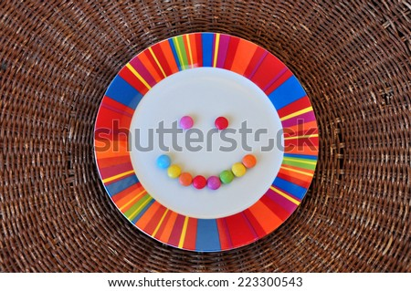 Plate with smiling face made from colorful candy. Abstract food background. - stock photo