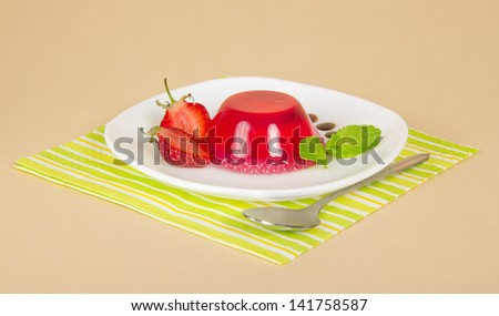 Plate with strawberry jelly, spoon and a striped napkin, on a beige background - stock photo