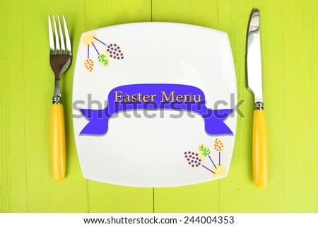 "Plate with text ""Easter Menu"", fork and knife on color wooden background - stock photo"