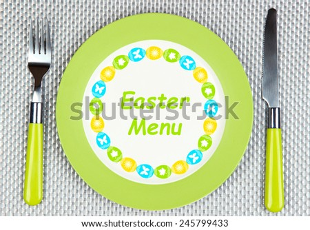 "Plate with text ""Easter Menu"", fork and knife on gray background - stock photo"