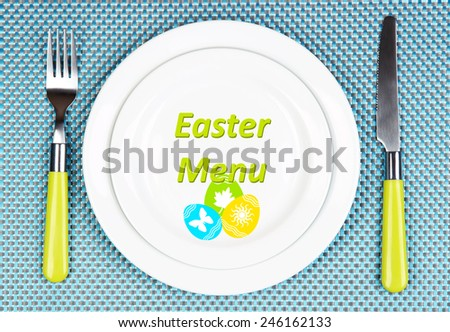 Plate with text Easter Menu, fork and knife on tablecloth background - stock photo