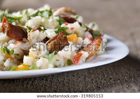 Plate with traditional spicy food called pilaf, on wooden background. Cooked with fried chicken, rice, garlic and carrot - stock photo