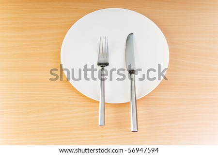 Plate with utensils on wooden table - stock photo