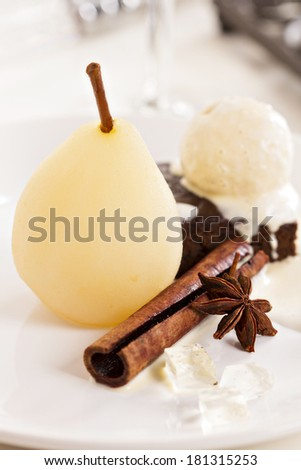 Plated dessert with poached pears, brownie and ice cream - stock photo