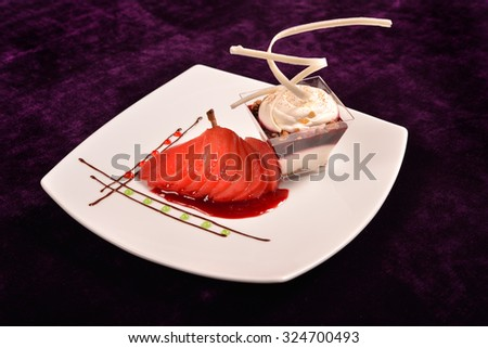 Plated dessert with poached pears in white porcelain plate - stock photo