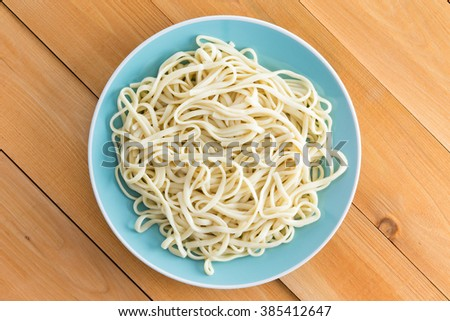 Plated of freshly boiled plain spaghetti served on a blue plate on a wooden garden table with diagonal planks, overhead view - stock photo
