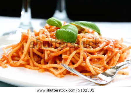 Plateful of delicious spaghetti with sprinkling of cheese and sprig of basil served on white plate with fork on the side. - stock photo