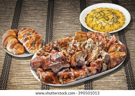 Plateful of spit roasted pork, Russian salad bowl and croissant puff pastry, set on woven parchment place mat. - stock photo