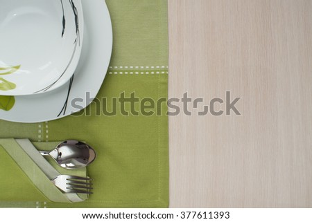 plates,a green tablecloth on the Wooden table fork spoon - stock photo