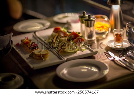Plates and Dishes on the table in luxury restaurant. Sushi roll with salad. Romantic dinner with ambient light from candle. - stock photo