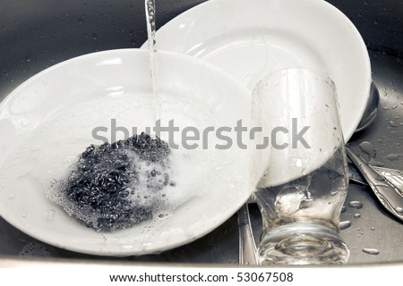 plates and glass washing in a sink - stock photo