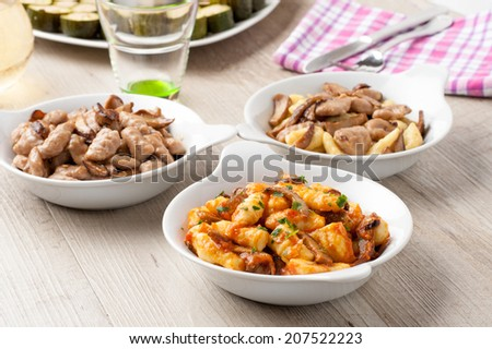plates of gnocchi served with different sauces - stock photo