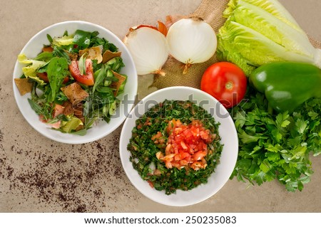 Plates of traditional Arabic salad fattouch and tabbouleh on a rustic background - stock photo