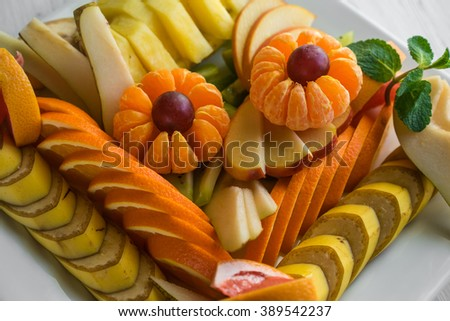 Platter of assorted fresh fruits on white plate - stock photo