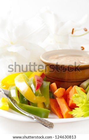 Platter of assortment of fresh vegetables with dipping sauce made of feta cheese - stock photo