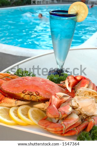 Platter of crab with lemons and parsley out by the pool - stock photo