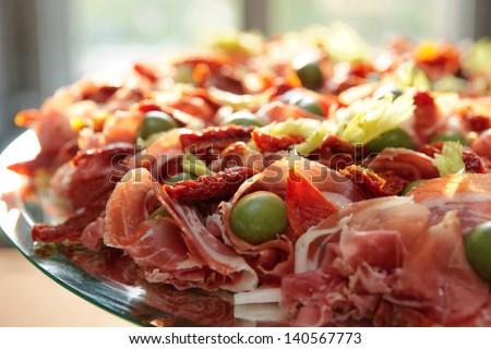 Platter with spanish cured ham on table - stock photo