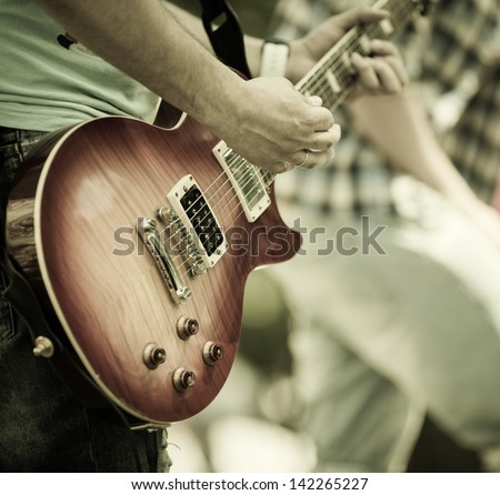 play on guitar, selective focus on part of strings - stock photo